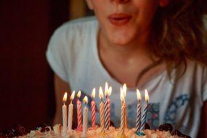 Frau bläßt Kerzen auf Geburtstagskuchen aus und Geburtstagsdj macht Musik